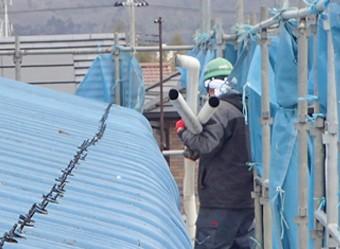古い雨樋を撤去する作業員